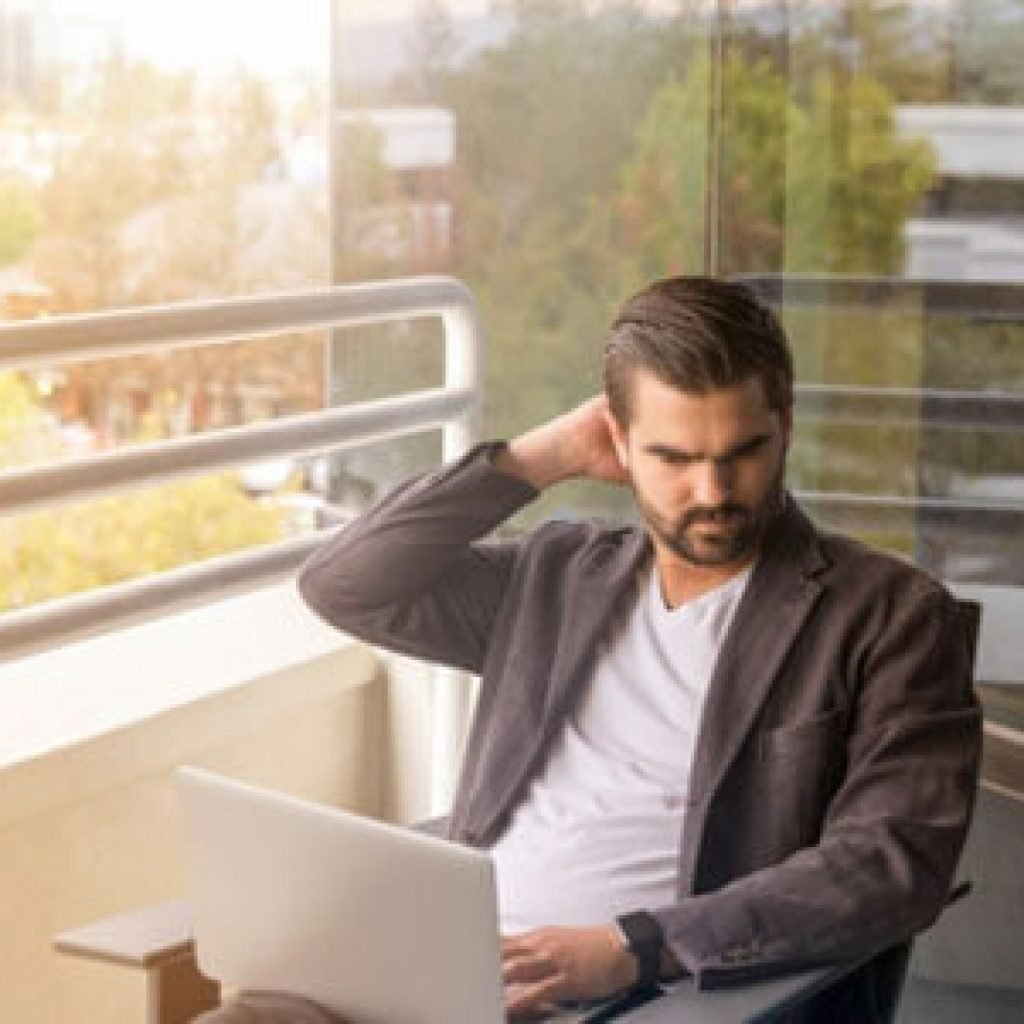 A man is using a laptop and is concerned about his online reputation.