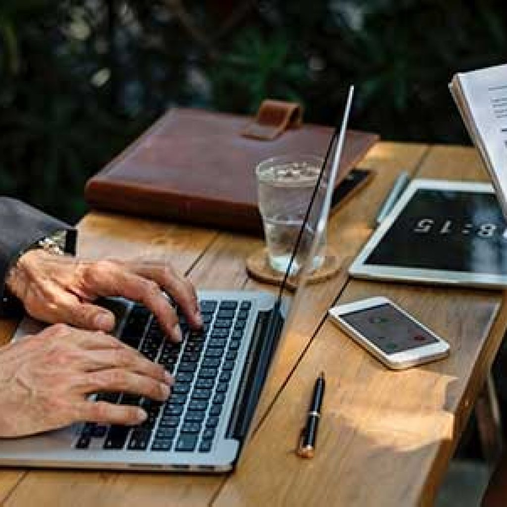A man is using a laptop to review his reputation online.